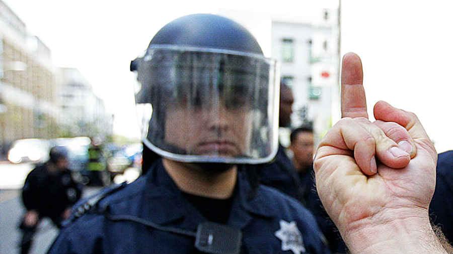 Запрещенный большой палец показывает полицейскому на улице
